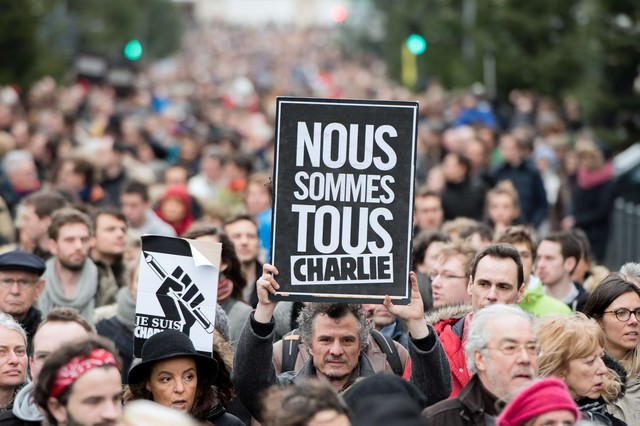 "A man holds a sign reading ""We all are Charlie"" on Januray 10, 2015, in the city of Lille, northern France as tens of thousands of people staged rallies across France following three days of terror and twin siege dramas that claimed 17 lives in total, including the victims of the first attack by armed gunmen on the offices of French satirical newspaper Charlie Hebdo in Paris on January 7. AFP PHOTO / DENIS CHARLET"