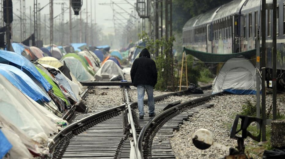 A man walks on the rail tracks of a train station turned into a makeshift camp crowded by migrants and refugees, at the northern Greek border point of Idomeni, Greece, Friday, April 29, 2016. Many thousands of migrants remain at the Greek border with Macedonia, hoping that the border crossing will reopen, allowing them to move north into central Europe. (AP Photo/Gregorio Borgia)