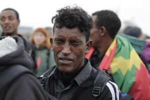 """A 16-year-old migrant from Ethiopia cries as he waits to register at a processing centre in the makeshift migrant camp known as """"the jungle"""" near Calais, northern France, Monday Oct. 24, 2016. Long lines of migrants waited calmly in chilly temperatures Monday to board buses in the French port city of Calais, as authorities began evacuating and dismantling the squalid camp they call home. (AP Photo/Emilio Morenatti)"""