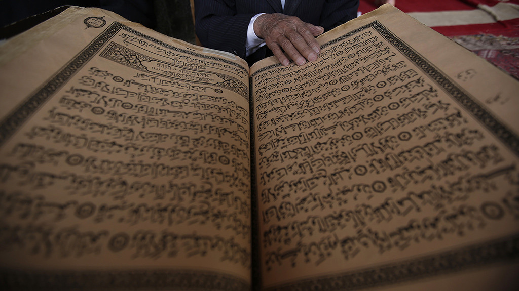 An elderly man reads verses of the Quran, Islam's holy book, on the first day of the fasting month of Ramadan in the Grand Mosque in the old city of Sanaa, Yemen, Monday, June 6, 2016 (AP Photo/Hani Mohammed)